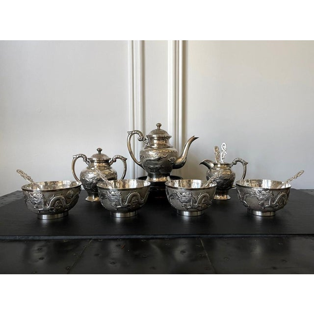 A Chinese export sterling silver tea set comprised of 13 pieces including tea pot, sugar, creamer, four tea bowls and six...