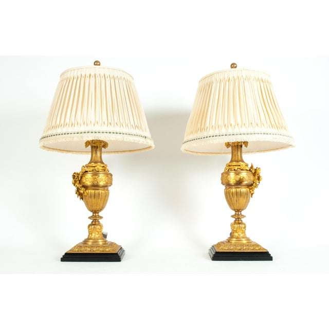 A pair of Louis XVI style gilt bronze task / table lamps. Each lamp is in excellent antique working condition, rewired for...