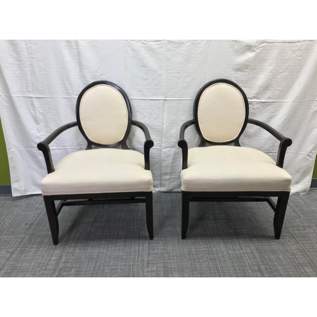 Pair of Barbara Barry oval X-back arm chairs in a cream upholstery. Made in the 2010s.