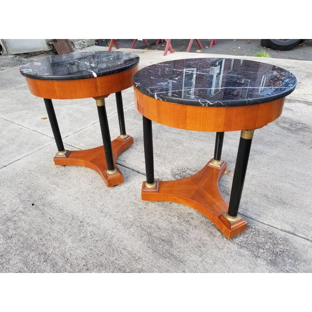 Pair of mid 20th century French Empire style round side tables with black marble tops. The column shaped black lacquered...