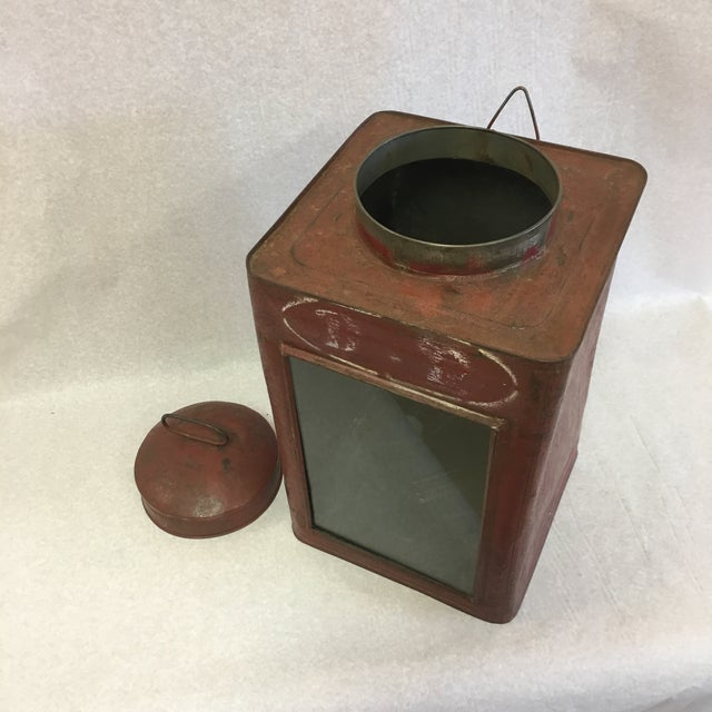 An antique lidded tin container with glass panel on one side.