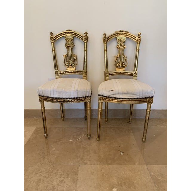 Antique pair of gilt wood, French Neoclassical Louis XVI Harp/Lyre back accent chairs. Hand carved chairs that have slight...