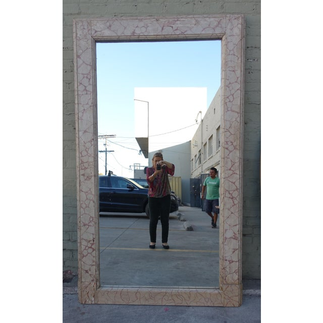 A monumental faux marble painted mirror.