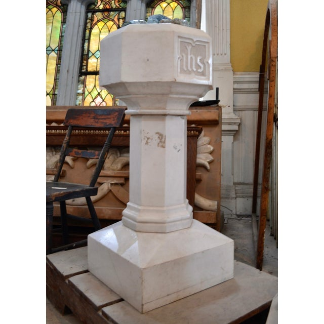 A hexagonal baptismal font on a square base from Baltimore City Church. The front panel bears the initials ihs (Iesus...