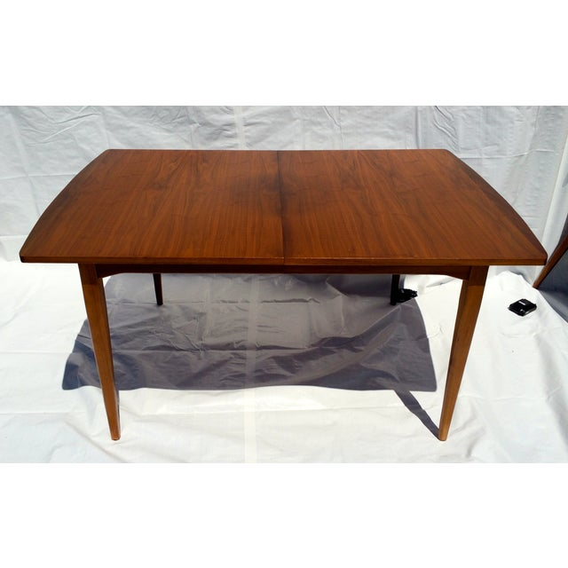 A great Mid-Century walnut table designed by Kipp Stewart for Drexel. One leaf is included. With leaf insert the table...