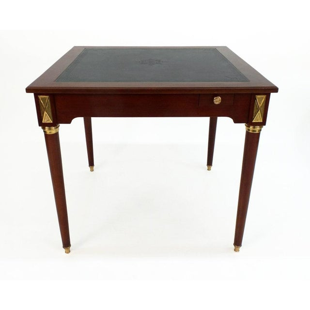 Louis XVI style game table having a blind tooled leather top, 4 small drawers and polished brass hardware: sabots,...
