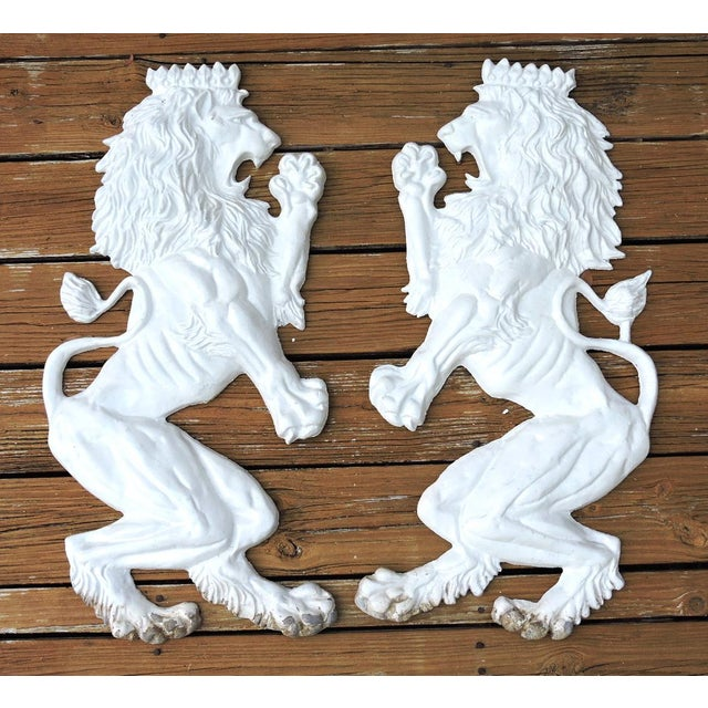 A regal pair of crowned white lion aluminium wall sculptures poised as rearing on their hind legs. They are weather...