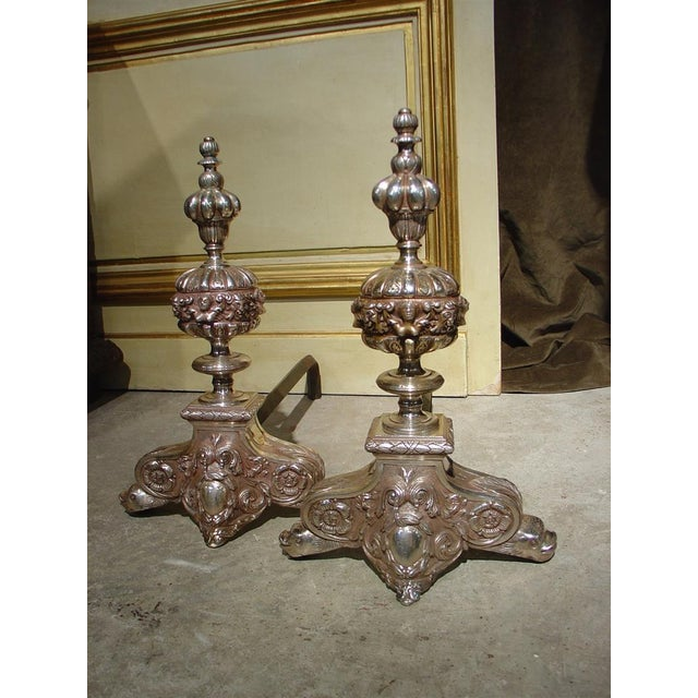 This pair of antique silvered bronze andirons has highly detailed repousse of floral and foliate motifs. The ornamentation...
