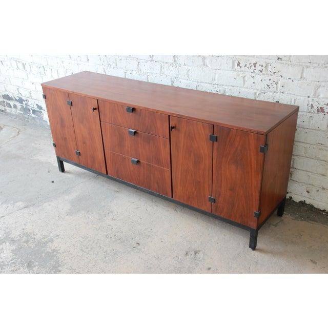 Offering a stunning mid-century modern walnut nine-drawer credenza or triple dresser designed by Milo Baughman for...