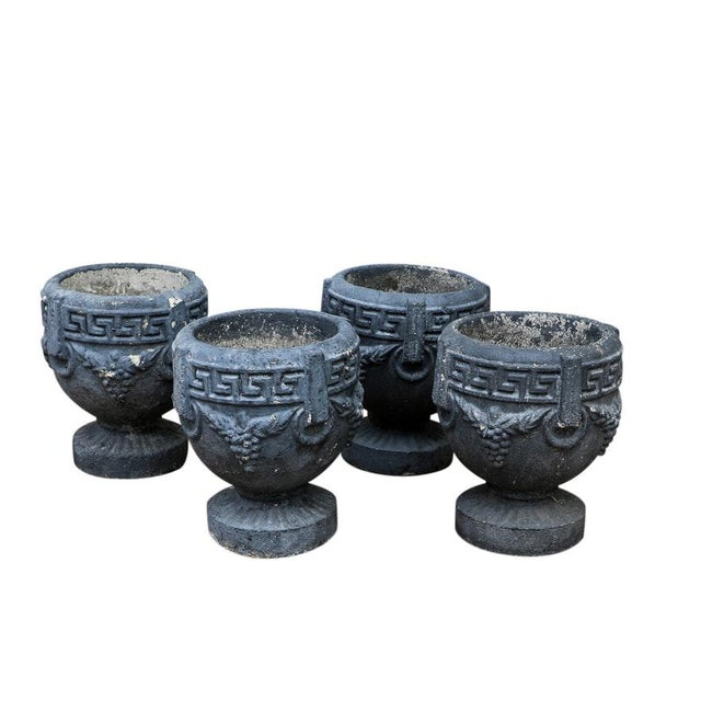 Matching neoclassical style black vintage cement pedestal shaped garden planters. Each has an identical cast design of...