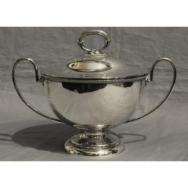 A handsome English soup tureen in neoclassical taste with reeded handles & beaded edges. Goldsmiths & Silversmiths LTD.,...