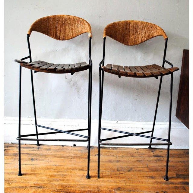 A Nice Pair of Mid-20th century Arthur Umanoff bar stools with iron bases, rushed back and wood slatted seats. Wear is...