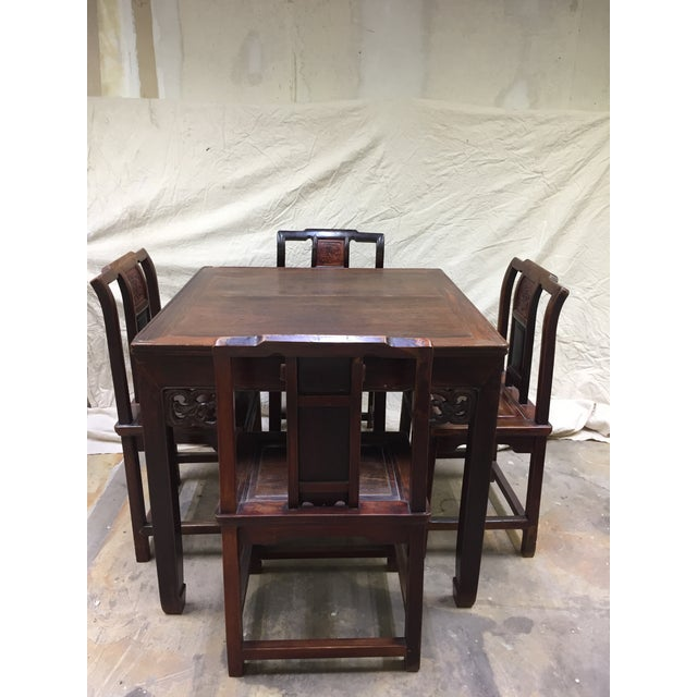Antique Chinese gaming table with four chairs. The table features four drawers. This gaming set has been well loved over...