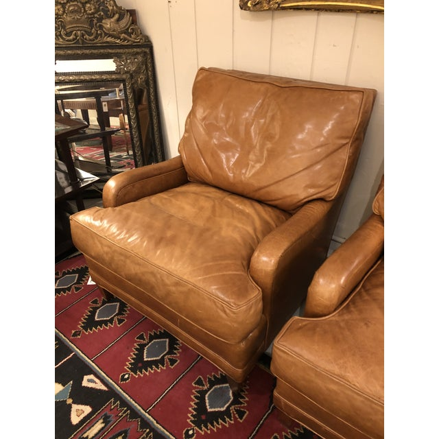 An enviably comfortable pair of luxurious butterscotch leather club chairs having Classic style and a top of the line...