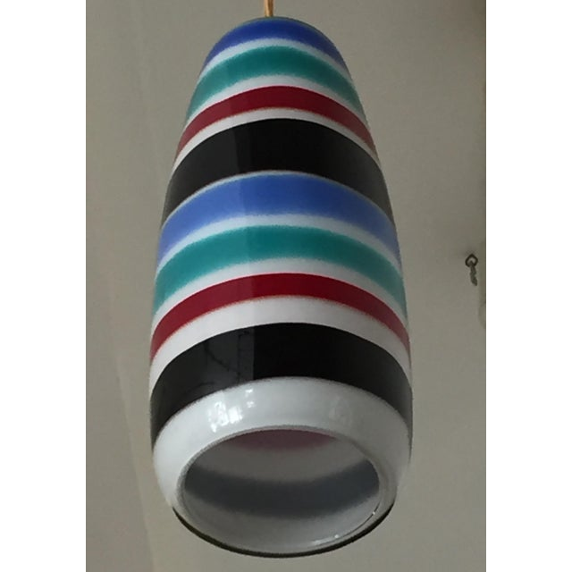 This colorful banded pendant lamp by massimo vignelli is ideal for a high ceilinged entry way. The bands of color adds a...