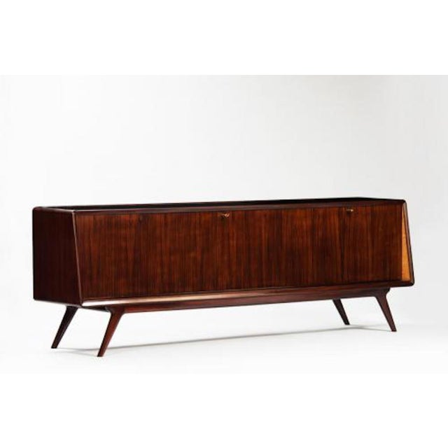 Dassi Mid-century sideboard featuring a body in Rosewood with shaped sides and a top and bottom shelf in black glass. The...
