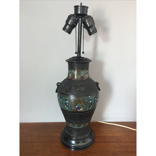 Offered is an antique champleve vase lamp. Beautiful colors, three men around pagoda scene repeated on front and back....