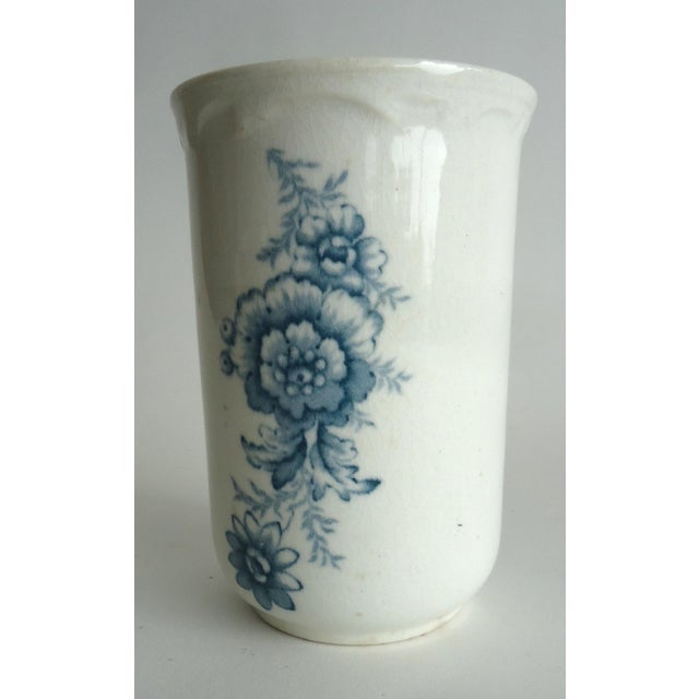 An antique stoneware beaker cup form vase with transfer blue floral decorations. This has a shabby chic style with some...