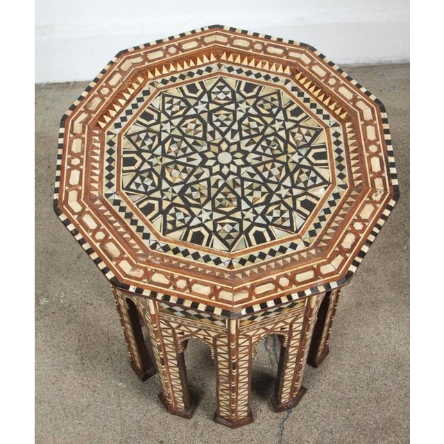 Syrian walnut octagonal side table inlaid with mother-of-pearl, ebony, horn and camel bone. Moorish arches on the eight...