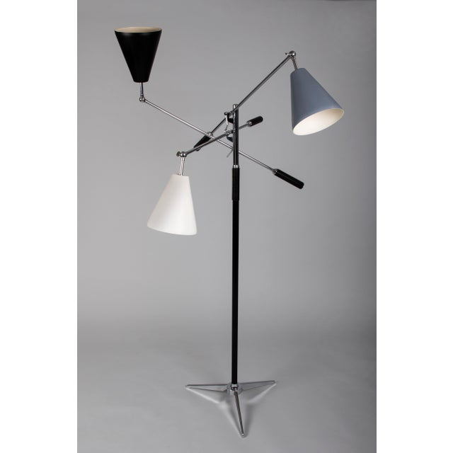 An architectural triennale floor lamp in the style of Angelo Lelli for Arredoluce, with three cone-shaped shades enameled...