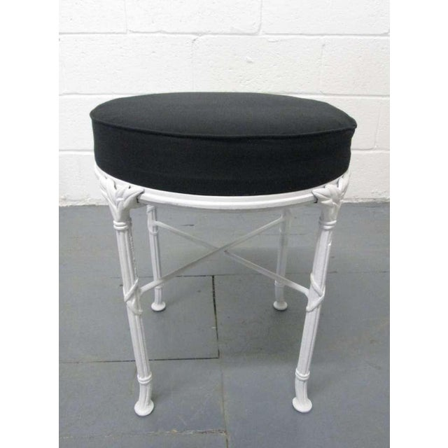 Pair Hollywood Regency Stools. Stools has black upholstered loosed cushioned seats. Frame has a painted white decorative...