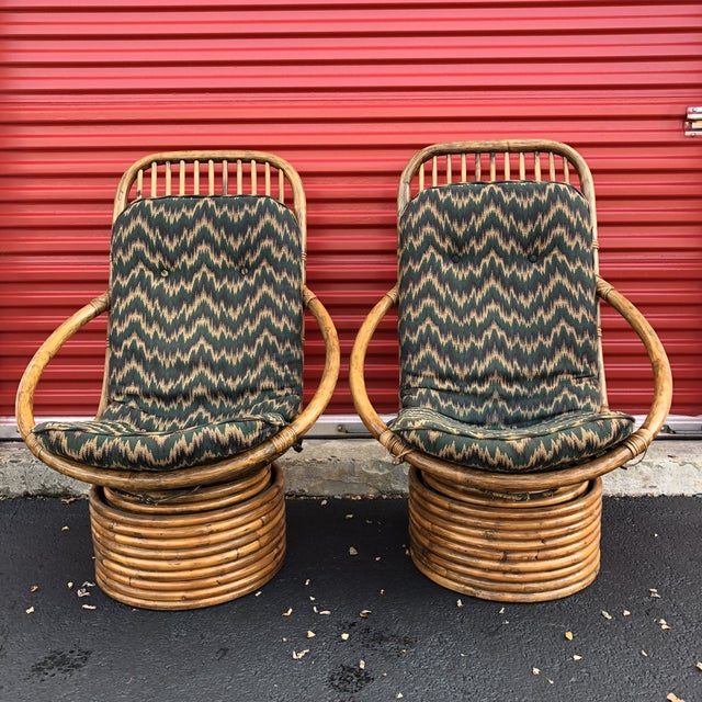 This pair of vintage Rattan lounge chairs feature removable cushions, swivel base, and original finish offering a boho...