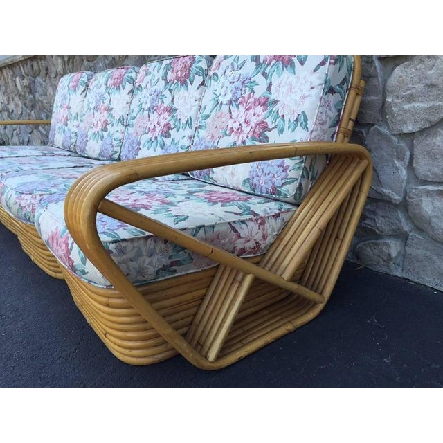 Square Pretzel rattan sofa style of Paul Frankl. Has a stacked rattan base and the sofa is in four sectional seating....