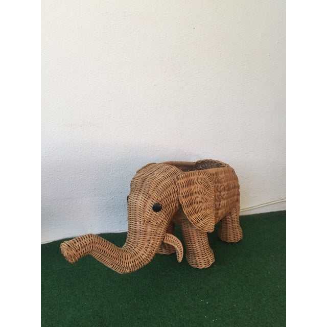 A fun circa 1970's Palm Beach style wicker elephant planter. Trunk is up!