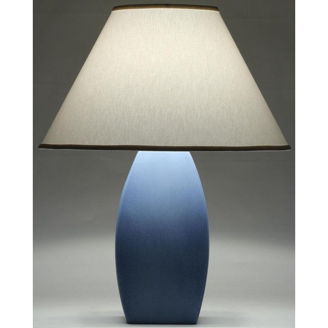 """A blue ceramic table lamp with white linen shade. Shade dimensions: 9"""" x 22""""x 12.5"""""""