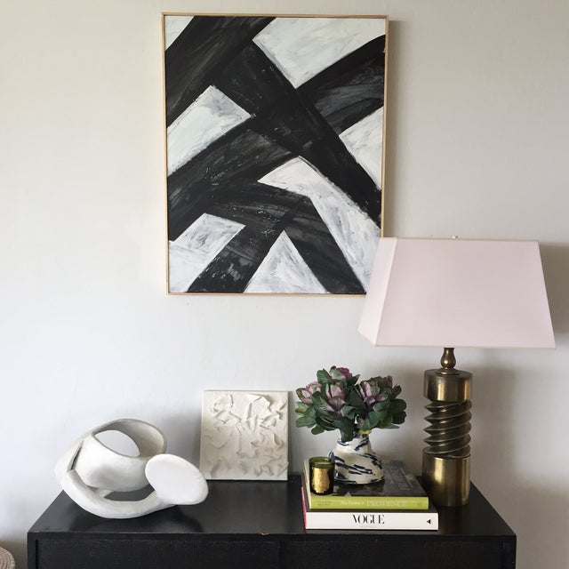 Layers of black and white acrylic, punctuated by sgraffito, produce a strikingly textured abstract composition in a simple...