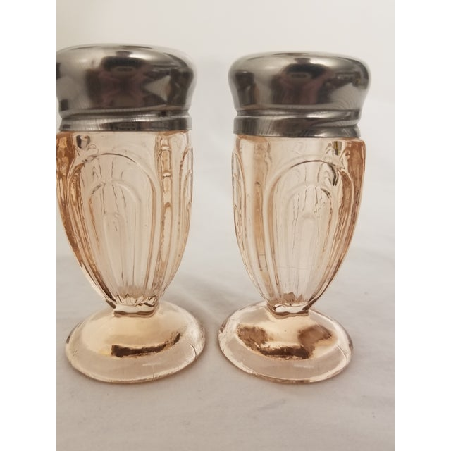 Vintage pressed glass salt and pepper shakers. Beautiful pink colored glass in an Art Deco pattern. Lids are made of...