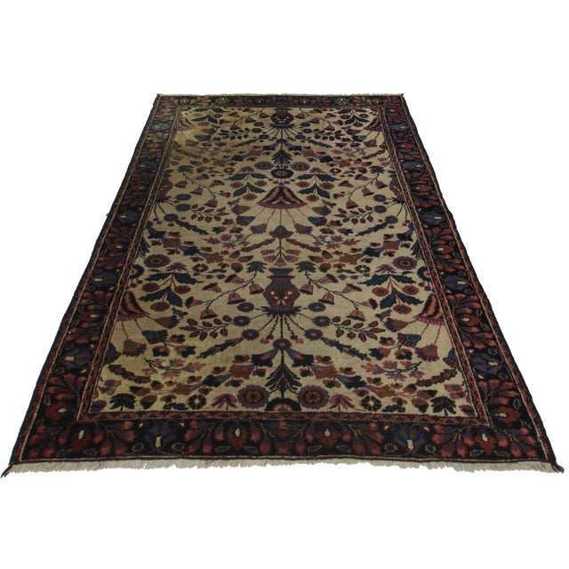 Crafted of hand-knotted wool, this Persian Mashad Rug features an all-over floral design.