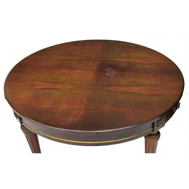 Gorgeous Louis XVI style/Empire style mahogany table from France, c. 1900. This table features a circular top with brass...