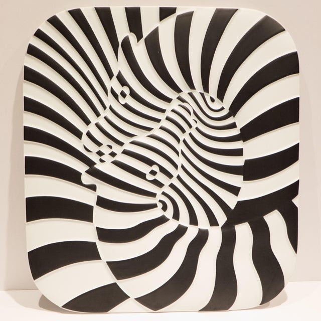 Op Art plaque or wall sculpture of two zebras in molded and painted porcelain. The wavy surface of the plaque emphasizes...