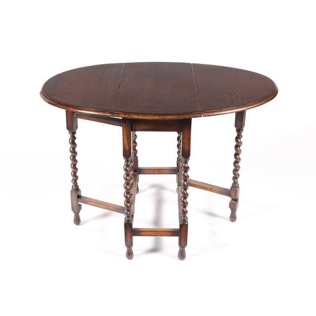 1920s English William and Mary-Style gate-leg table featuring spiral legs, oval leaves and an antiqued oak patina.