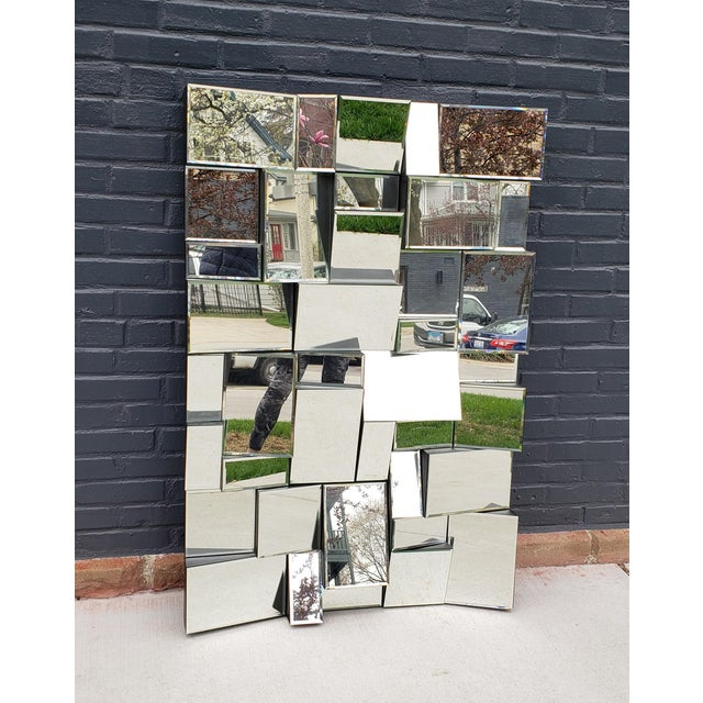 A three dimensional mirror cubist mirror that creates the most brilliant patterns of images from the various pieces of cut...