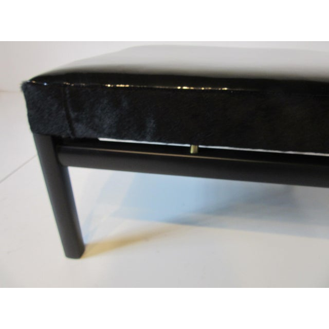 A ebony finished wood framed ottoman with black patent leather top with the sides trimmed in black pony hide and brass...