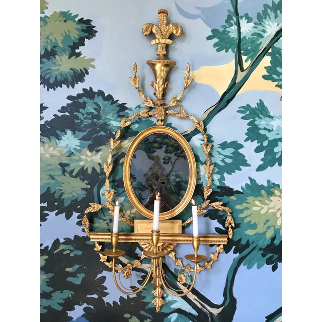 This extremely rare pair of giltwood girandole mirrored wall sconces is English and was produced in the early 19th century...