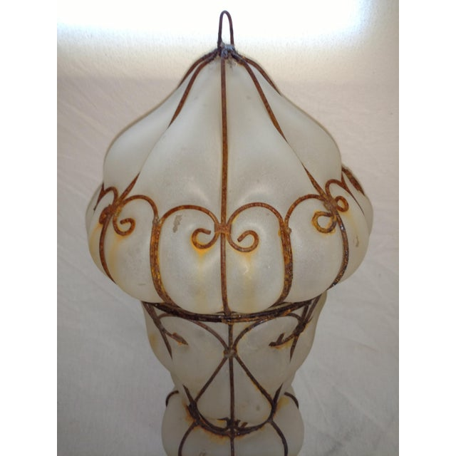 This large 1960's lantern was made in Egypt. The glass was blown into a wire mold. A wire and a screw hold the two halves...
