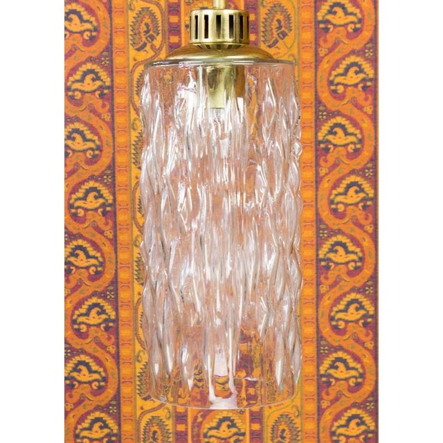 A hanging light fixture from France, circa 1960. The textured glass is attached to a brass stem. The overall height is...