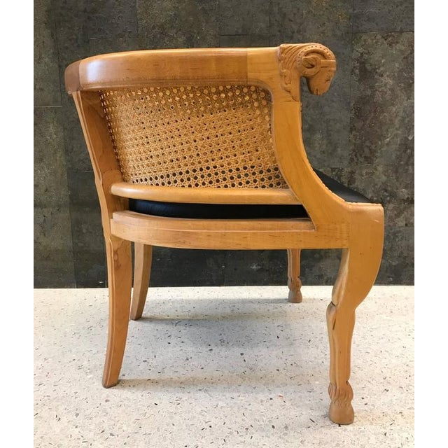 Pair of neoclassical style ram's head chairs with black leather seats. Chairs has a caned back and sides with a solid...