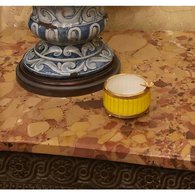 An antique yellow ashtray by Murano with ribbed glass and gilt trim. Sitting on three ball feet. Circa 1850, Italy.