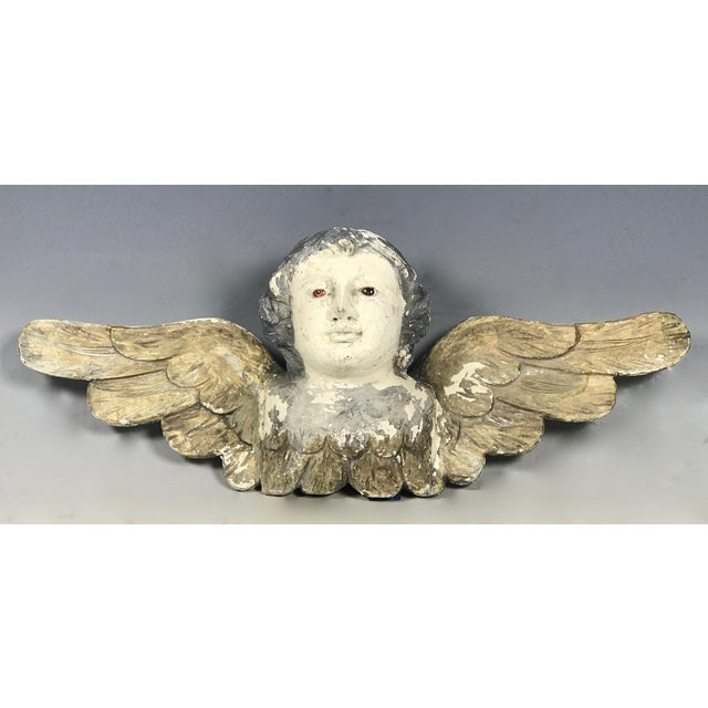 Handcarved wood Cherub with long wings. Made of wood and pigment with glass eyes. Very good and excellent condition.