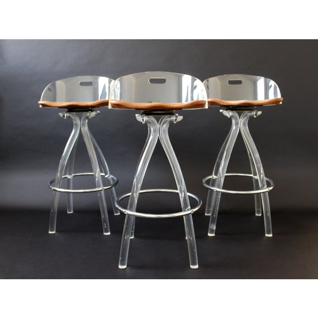 For your consideration is a spectacular set of three bar or counter stools, made of clear lucite, with wooden saddle seats...