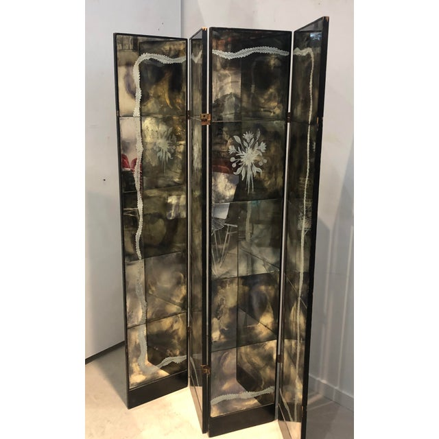 Vintage Italian four panel mercury mirror screen with reverse painted foliate motif. The screen is hinged and the backside...