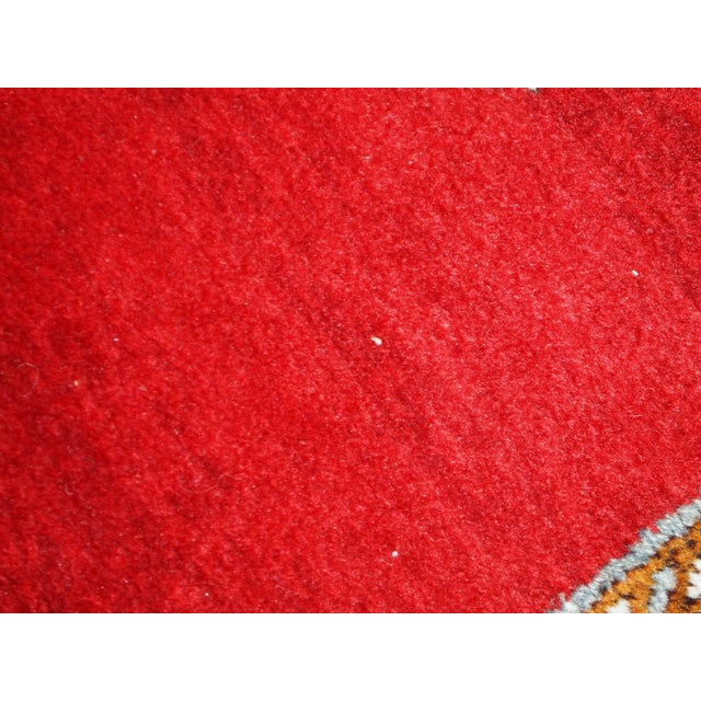 Vintage wool Turkish Oushak runner in original good condition. It is in bright red shades with sky blue medallions. The...