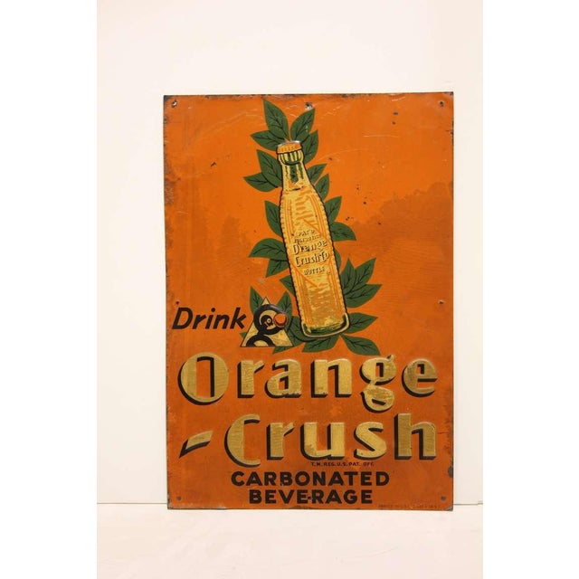 1920's American original advertising embossed tin sign for Orange Crush. This piece would look great in an entertainment...