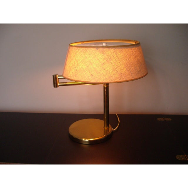 Iconic desk lamp by Walter Von Nessen. This lamp features heavy brass base with offset upright, tight swing arm, dual...