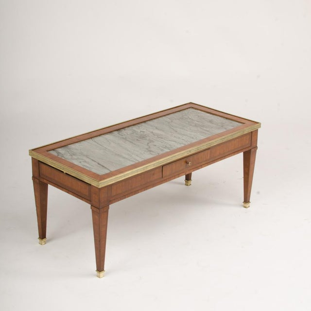 A French Directoire style mahogany coffee table C 1940, with grey marble top, one central drawer with two lateral extensions.