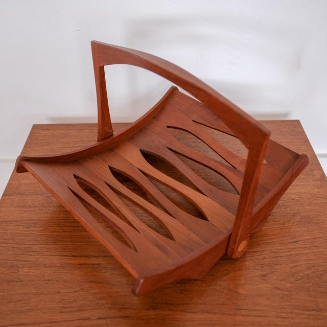 Magazine rack designed by Jens Quistgaard for Dansk. Staved solid teak frame with collapsible handle. Branded on the...